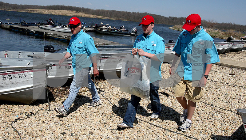 Rob Winner – rwinner@kcchronicle.com<br /> Marmion coach Scott Oesterlin (from left), Bradford Warland, and Casey Smith carry a bag containing a large mouth bass which Warland caught during Friday's IHSA fishing sectional at Shabbona Lake on Friday afternoon. The fish, which was caught by Marmion freshman Bradford Warland, weighed in at 3.60.<br /> 04/24/2009