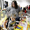 Rob Winner – rwinner@daily-chronicle.com<br /> Diana Beams, of Community Coordinated Child Care, helps a group of children pick out a donated book to take home at the 4C office on Tuesday morning in DeKalb.<br /> 11/17/2009