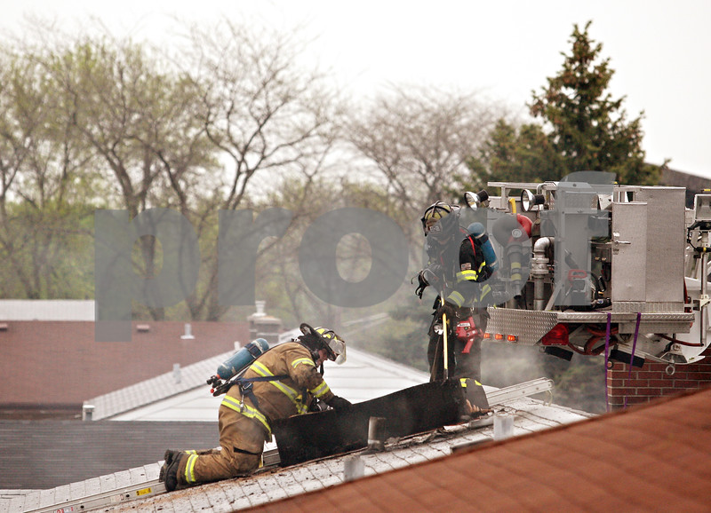 Beck Diefenbach  -  bdiefenbach@daily-chronicle.com<br /> <br /> Firefighters tear open the roof of the fire damaged Omega Delta Fraternity house on the 800 block of Hillcrest Road in DeKalb, Ill.