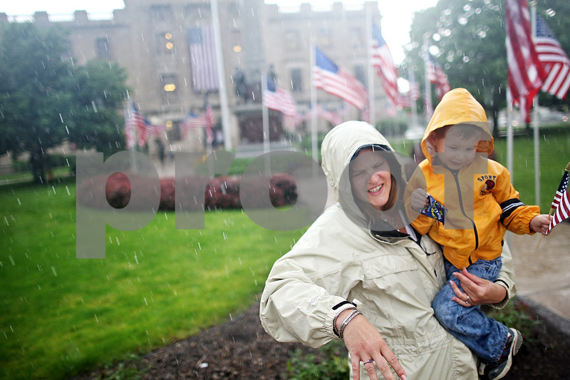Beck Diefenbach  -  bdiefenbach@daily-chronicle.com<br /> <br /> A woman struggles to get her children out of the rain while waiting for the return of the Sycamore National Guard Unit outside the DeKalb Courthouse in Sycamore, Ill., on Monday June 1, 2009.