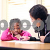 Beck Diefenbach  -  bdiefenbach@daily-chronicle.com<br /> <br /> Left, Brimonet Smith, 9, gets assistance on her homework from Evie Cordero, 15, of the Philippine Youth Leadership Program at Hope Haven in DeKalb, Ill., on Monday April 13, 2009.