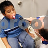 Rob Winner – rwinner@daily-chronicle.com<br /> <br /> Jovanny Sangabriel, 5, of Sycamore, sticks out his tongue during an examination with physician assistant David Wester at the new Community Cares Clinic in DeKalb on Monday October 19, 2009.