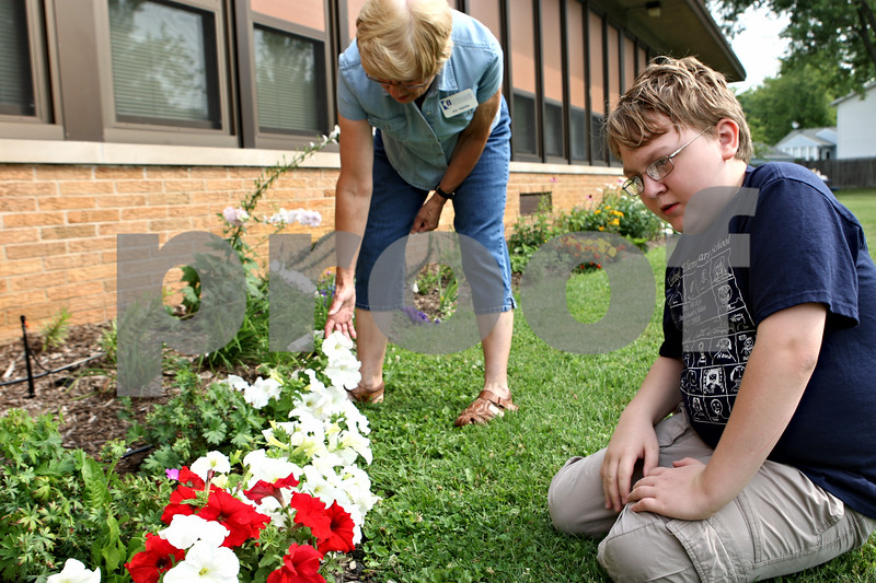Rob Winner – rwinner@daily-chronicle.com<br /> Joy Gulotta (left), with the University of Illinois Extension, helps show Jeffrey Fleming, 10, how to deadhead flowers at Littlejohn Elementary School on Tuesday morning in DeKalb.<br /> 08/04/2009