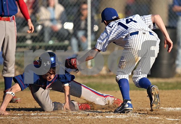 Beck Diefenbach  -  bdiefenbach@daily-chronicle.com<br /> <br /> Newark's Cody Walker, left, slips past Hinckley-Big Rock pitcher Colton Craig (14) to steal home during the top of the sixth inning in Big Rock, Ill., on Thursday April 16, 2009.