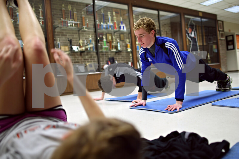 Beck Diefenbach – bdiefenbach@daily-chronicle.com<br /> <br /> DeKalb High School senior Luke Dubrick does push ups with the rest of his long distance team during practice at DeKalb High School in DeKalb, Ill., on Tuesday March 10, 2009.
