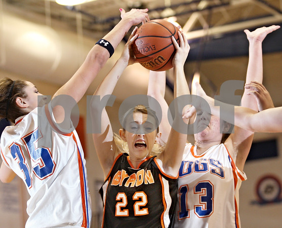Beck Diefenbach  -  bdiefenbach@daily-chronicle.com<br /> <br /> Byron's Meghan Fits (22) keeps the ball from Genoa-Kingston forward Alexis Carroll (35) and forward Mariah Sartorius (13) during the second quarter of the game at Genoa-Kingston High School in Genoa, Ill., on Tuesday Jan. 27, 2009. Byron beat GK 41 to 38.