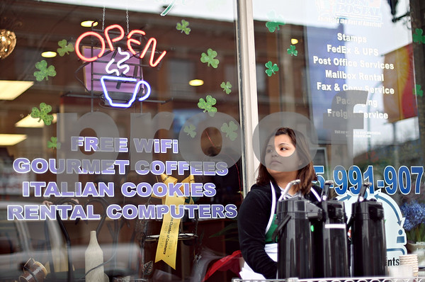 Beck Diefenbach  -  bdiefenbach@daily-chronicle.com<br /> <br /> Mayeli Hidalgo, an employee for Tuscani Cyber Cafe, waits for passer-bys to offer them free tastes of the new company's Italian coffee in Sycamore, Ill., on Wednesday March 18, 2009.