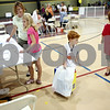 Rob Winner – rwinner@daily-chronicle.com<br /> On Tuesday afternoon in the field house at Sycamore Hight School, Cameron Kruskol (center), 4, holds a box of school supplies for his brother Kyle (right), 8, as their mother Julie registers Kyle and his sister Kelsie, 10, for school at Southeast School.<br /> 08/11/2009