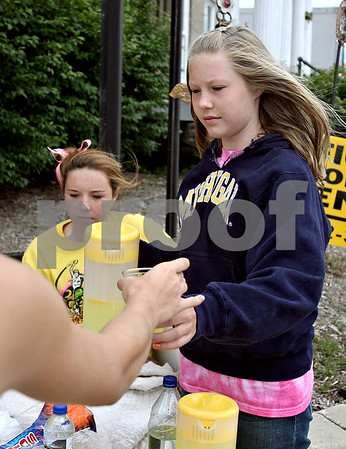 Rob Winner – rwinner@daily-chronicle.com<br /> Lilia Edwards, 12, serves a glass of lemonade to a customer on Friday afternoon at the corner of Somonauk and Elm streets in Sycamore. Sisters Lilia and Elena Edwards qualified for the Junior Olympic nationals with the Huskie Track Club and are now trying to raise the funds to get there.<br /> 07/17/2009