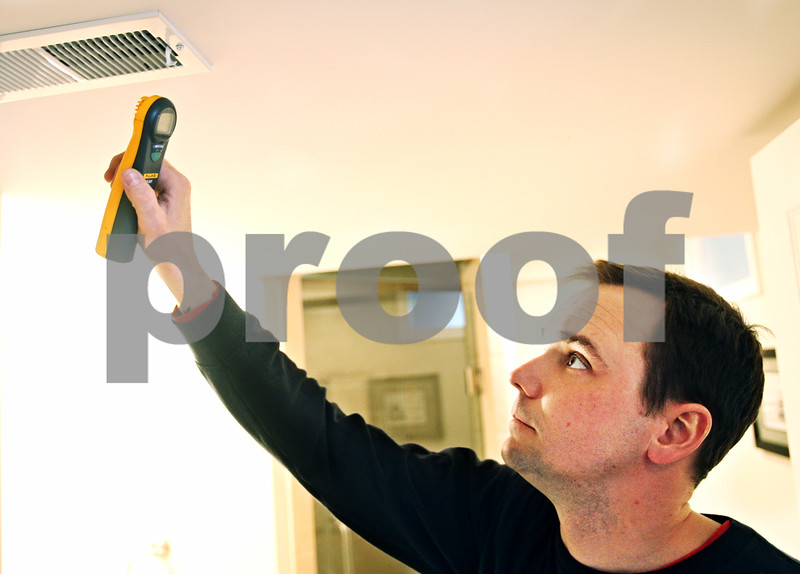Beck Diefenbach  -  bdiefenbach@daily-chronicle.com<br /> <br /> Ron Breese, of Breezy's Heating and Air Conditioning, uses a carbon monoxide detector to test the air quality from a vent as part of a preseason clean and check of a home in DeKalb, Ill., on Monday Feb. 9, 2009.