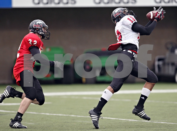 Beck Diefenbach  -  bdiefenbach@daily-chronicle.com<br /> <br /> Northern Illinois wide receiver Willie Clark (12) catches ball ahead of defensive back John Kremer (22) during practice at Huskie Stadium in DeKalb, Ill., on Tuesday April 14, 2009.
