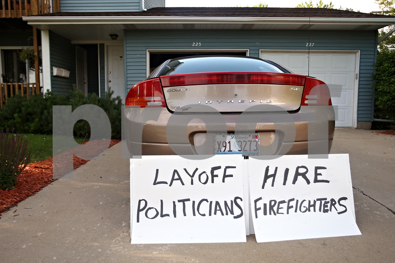 """Beck Diefenbach  -  bdiefenbach@daily-chronicle.com<br /> <br /> A sign protesting the possible layoffs of DeKalb firefighters sits next to car at the house of Fred Fletcher in DeKalb, Ill., on Monday June 22, 2009. """"I stand behind these (firefighters),"""" Fletcher said. """"They work hard."""""""