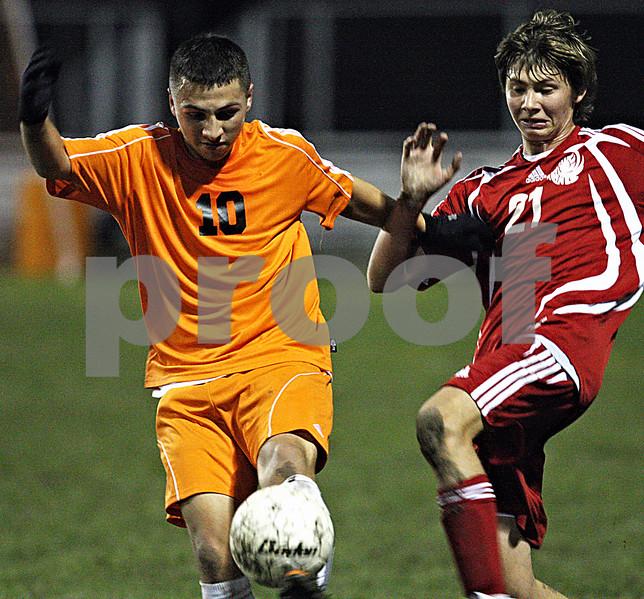 Rob Winner – rwinner@daily-chronicle.com<br /> DeKalb's Eric Galvan (left) and a Marian defender battle for possession.
