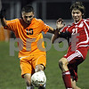 Rob Winner – rwinner@daily-chronicle.com<br /> DeKalb's Eric Galvan (left) and a Marian defender battle for possession.