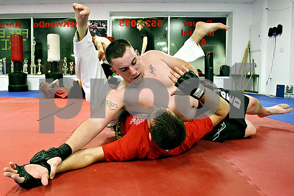 Rob Winner – rwinner@daily-chronicle.com<br /> Brandon Burnett (top), of Aurora, and Master Marvin Steele practice mixed martial arts at Power Martial Arts in Plano on Tuesday evening.<br /> 11/17/2009