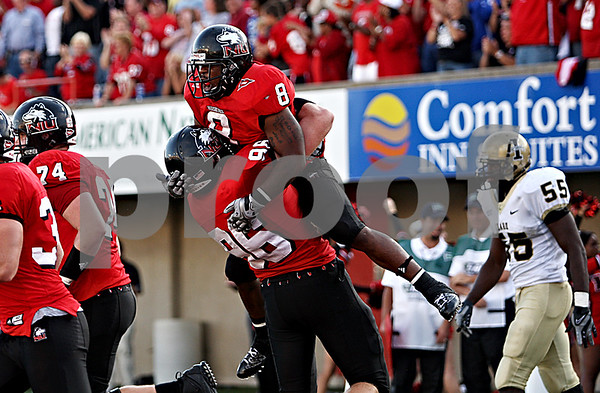 Rob Winner – rwinner@daily-chronicle.com<br /> After running into the end zone for a two point conversion, Me'co Brown (8) jumps into the arms of Bryan Beckner. The two point conversion got the Huskies within three.<br /> 09/26/2009
