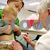 Rob Winner – rwinner@daily-chronicle.com<br /> Charlie Rouw, 21 months of Sycamore, sits in his mother's lap, Rhiannon, while receiving an H1N1 vaccination at the DeKalb County Health Department on Thursday December 17, 2009 in DeKalb, Ill.