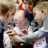 Rob Winner – rwinner@daily-chronicle.com<br /> (From left to right) Kalob Kvopil, 4, Nathan McKinley, 6 months, Deb Baird and Ryan Hein, 4, look through one of the books that was given to them by Community Coordinated Child Care on Monday afternoon at the 4C office located in DeKalb.<br /> 11/17/2009