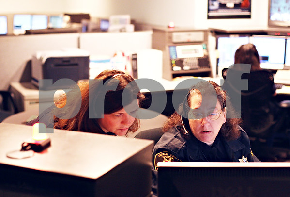 Beck Diefenbach  -  bdiefenbach@daily-chronicle.com<br /> <br /> Deputies Lisa Winckler, left, and Kim Stiles discuss a 911 call as telecommunicators for the DeKalb County Sheriffs Office in Sycamore, Ill., on Friday April 10, 2009.