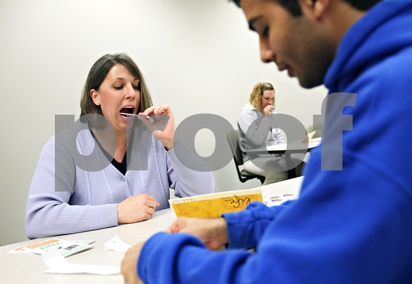 Beck Diefenbach  -  bdiefenbach@daily-chronicle.com<br /> <br /> Northern Illinois University staff member Shannon Gates swabs the inside of her cheeks as part of joining the National Marrow Donor Program in Barsema Hall on the NIU campus in DeKalb, Ill., on Thursday April 30, 2009.