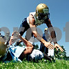 Rob Winner – rwinner@daily-chronicle.com<br /> Jace Quimby (top) jumps over teammate Payton Luepkes while doing a drill during a Hiawatha football practice recently.<br /> 08/12/2009
