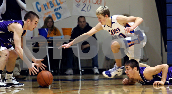 Beck Diefenbach  -  bdiefenbach@daily-chronicle.com<br /> <br /> Genoa-Kingston center Ace McCarty (40) and Rockford Lutheran guard Justin Miller (20) converge on a loose ball during the first quarter of the game at GK in Genoa, Ill., on Friday Jan. 16, 2009. Lutheran beat GK 46 to 39.