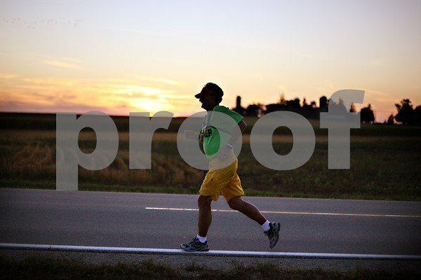 Beck Diefenbach  -  bdiefenbach@daily-chronicle.com<br /> <br /> David Kuhn trains for the Chicago Marathon on Nelson Road southwest of DeKalb on Wednesday Sept. 30, 2009. Although legally blind, Kuhn is able to make out the white line on the road as a guide.