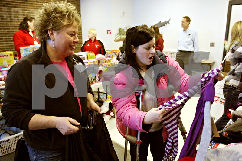Rob Winner – rwinner@daily-chronicle.com<br /> Deanna Carby (left), a volunteer shopper, helps Shena Fritsch, of Sandwich, pick out some items for Fritsch's seven year old daughter as Toys for Tots were donated at the YMCA in DeKalb, Ill. on Tuesday December 22, 2009.