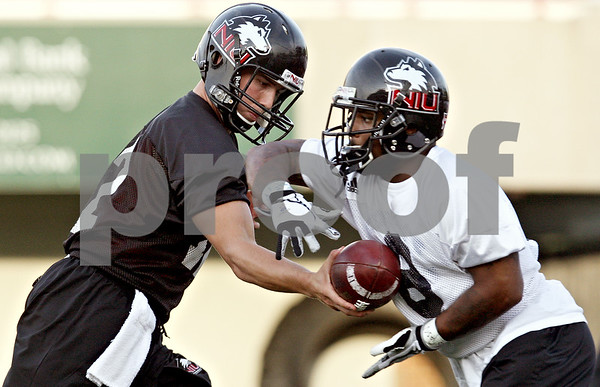 Rob Winner – rwinner@daily-chronicle.com<br /> Chandler Harnish (left) hands off to Me'co Brown during NIU football practice on Thursday night.<br /> 08/06/2009