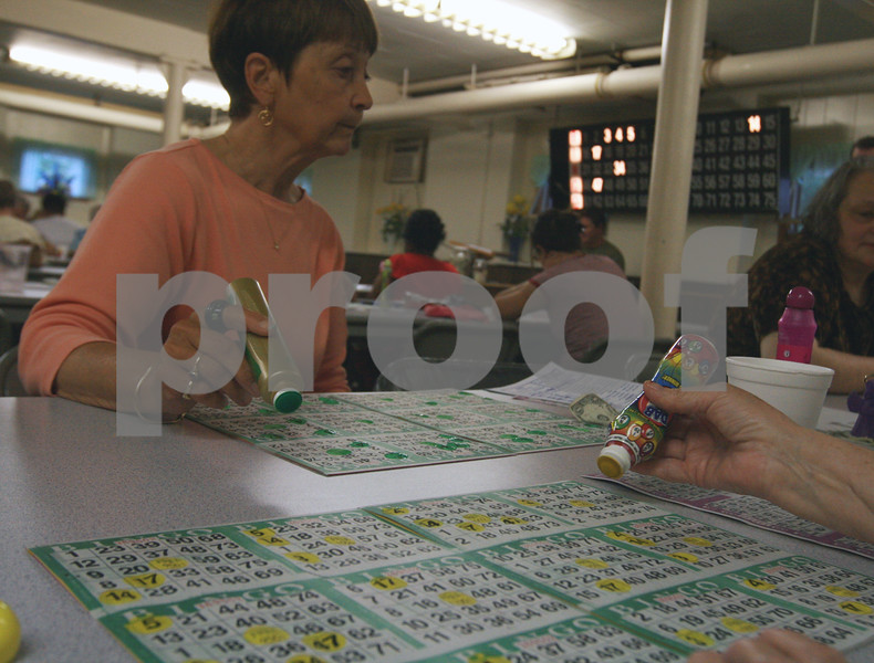 Randi Stella – rstella@daily-chronicle.com<br /> <br /> Carol Niles, 66, peeks at another's bingo card during Bingo Night at St. Mary's school in DeKalb, Ill., June 8th, 2009.