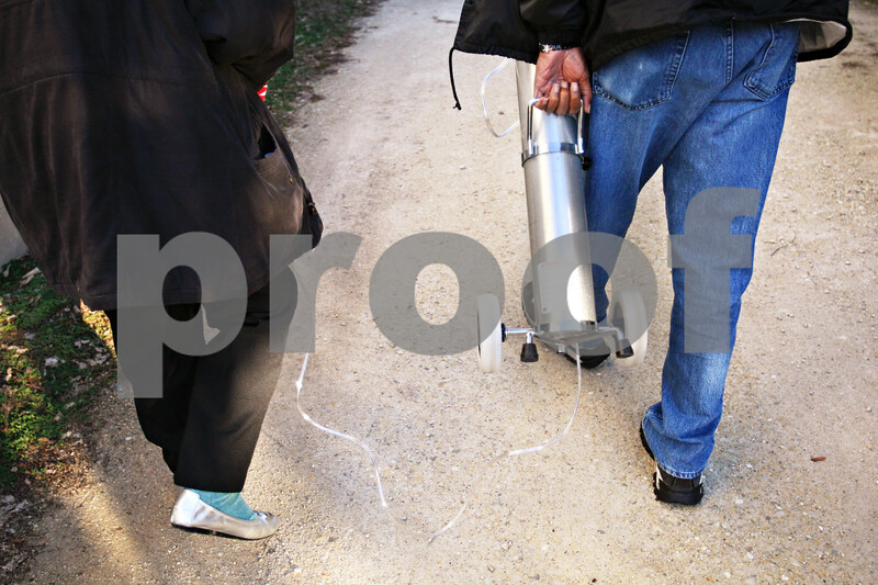 Beck Diefenbach  -  bdiefenbach@daily-chronicle.com<br /> <br /> Voluntary Action Center driver Larry Weaver, right, caries the oxygen tank for Cathy Marlow, of DeKalb, as he walks her to her door after driving her home  from a therapy session on Tuesday Dec. 1, 2009.