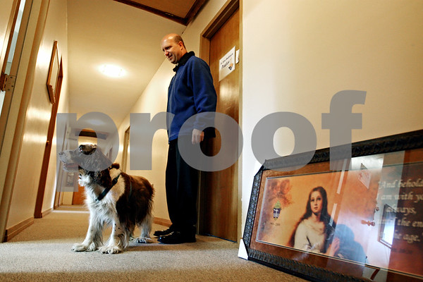 Rob Winner – rwinner@daily-chronicle.com<br /> Father Ken Anderson of St. Mary Catholic Church in DeKalb and his dog Kosia, an English Springer Spaniel. return to their room after a walk outside.<br /> 09/30/2009
