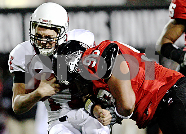 Rob Winner – rwinner@daily-chronicle.com<br /> Ball State quarterback Tanner Justice gets hit by Northern's D.J. Pirkle during the second quarter. NIU defeated Ball State 26-20 on Thursday night in DeKalb.<br /> 11/12/2009