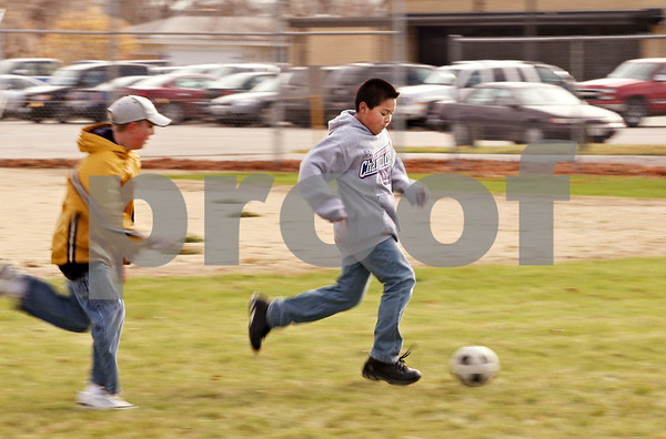 Beck Diefenbach  -  bdiefenbach@daily-chronicle.com<br /> <br /> Fifth grader Enrique Flores dribbles the ball down field as part of a micro soccer tournament during physical education class at Hiawatha Elementary School on Wednesday Nov. 4, 2009.