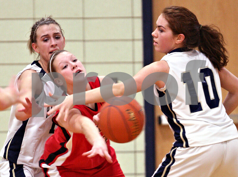 Beck Diefenbach  -  bdiefenbach@daily-chronicle.com<br /> <br /> Earlville-Leland's Jessica Miller (3, center) slips the ball past Hiawatha's Cassie Lutz (10) during the second quarter of the game at Hiawatha High School in Kirkland, Ill., on Monday Dec. 14, 2009.