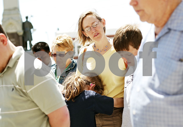 Beck Diefenbach  -  bdiefenbach@daily-chronicle.com<br /> <br /> Susan Davis, of Sycamore, is held by her daughter, Sarah, 8, during a group prayer as part of National Day of Prayer outside the DeKalb County Courthouse  in Sycamore, Ill., on Thursday May 7, 2009.