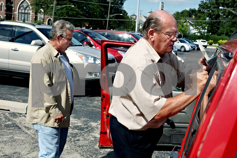Rob Winner rwinner@daily-chronicle.com<br /> Leo Elliott (right), of the Mike Mooney auto dealership in DeKalb, records the mileage of Darren Watson's 1993 Jeep Cherokee on Monday afternoon. Watson was taking advantage of the last day of the 'Cash for Clunkers' program.<br /> 08/24/2009