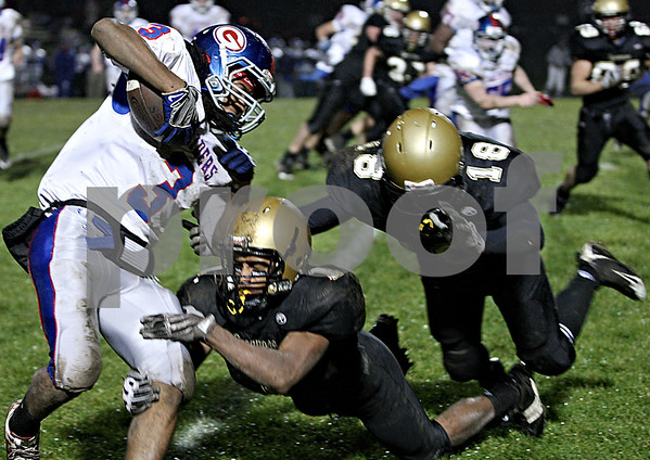 Rob Winner – rwinner@daily-chronicle.com<br /> <br /> Glenbard South's Connor Douglas is tackled by Sycamore's Marckie Hayes (1) and Sam McRickard during the first half.<br /> <br /> 10/23/2009