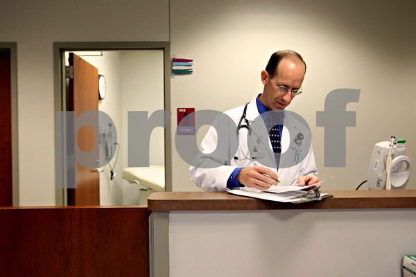 Rob Winner – rwinner@daily-chronicle.com<br /> <br /> Physician assistant David Wester fills out some paperwork at the new Community Cares Clinic in DeKalb on Monday October 19, 2009.