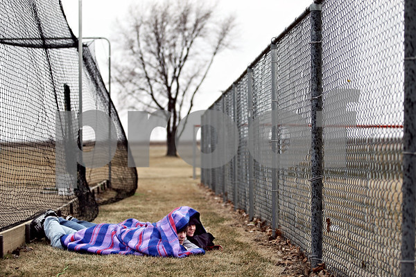 Beck Diefenbach  -  bdiefenbach@daily-chronicle.com<br /> <br /> Bobby Schlick, 17, of Sycamore, Ill., and his friend Alex Robbins, of Huntley, Ill., try to keep warm while watching the DeKalb High School softball game at DeKalb High School in DeKalb, Ill., on Monday March 23, 2009.