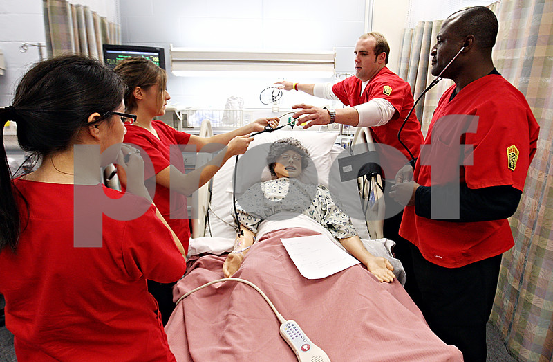 Rob Winner – rwinner@daily-chronicle.com<br /> <br /> Nursing students (from left to right) Rose Vargas, Candice Duarte, Dan Cwik, and Donald Walker work together to diagnose Maribel, a high fidelity simulation mannequin, at the NIU School of Nursing and Health Studies on Friday October 16, 2009.