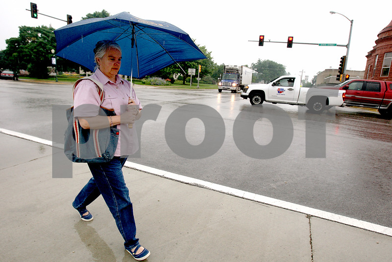 Rob Winner – rwinner@daily-chronicle.com<br /> On a rainy Friday morning in Sycamore, Sue Breese, of DeKalb, crosses Main Street along State Street on her way to the post office.<br /> 07/10/2009