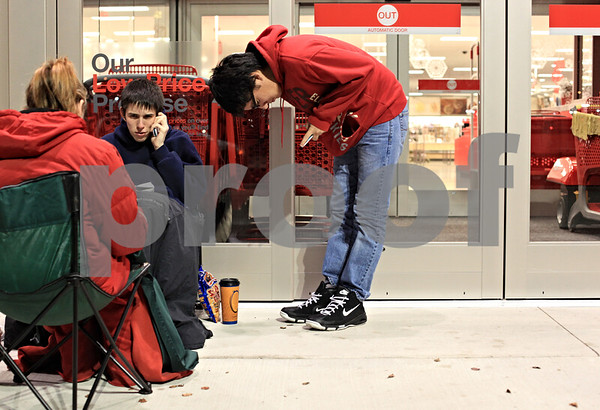 Beck Diefenbach  -  bdiefenbach@daily-chronicle.com<br /> <br /> Andrew Harvey (center), 16, and his friend Brian Mitchell, 16, both of DeKalb, wait overnight for the new Target store to open in DeKalb, Ill., on Friday Nov. 27, 2009.