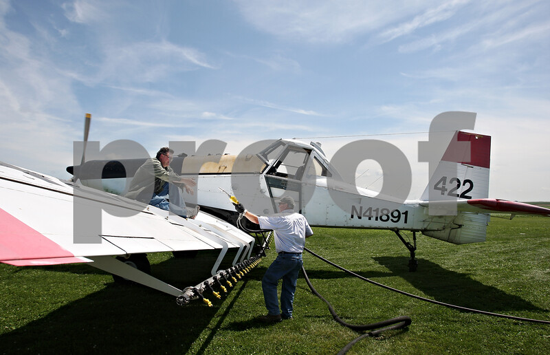 Beck Diefenbach  -  bdiefenbach@daily-chronicle.com<br /> <br /> Crop dusting pilot Nate Brown, left, gets help refueling from Brad Dicky, of Hintzsche Fertilizer, during a quick fuel and fertilizer stop at Hendrickson Flying Service outside of Rochelle, Ill., on Monday July 27, 2009.
