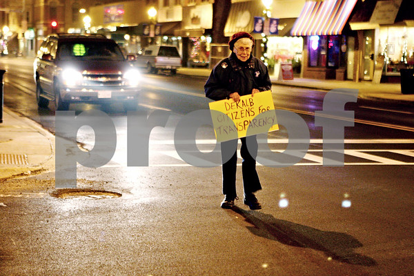 Rob Winner – rwinner@daily-chronicle.com<br /> Cecile Meyer heads east on Lincoln Highway toward City Hall in DeKalb after protesting at the corner of Lincoln Highway and First Street.<br /> 11/23/2009