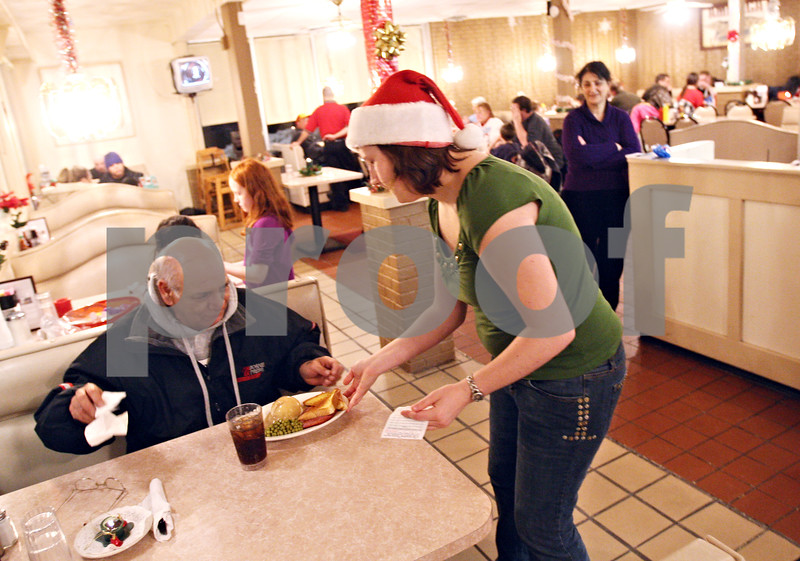 """Beck Diefenbach  -  bdiefenbach@daily-chronicle.com<br /> <br /> Tanya Ottoman-Towne serves dinner to Ricky Rodriguez during the community dinner at Flippin Eggs in DeKalb, Ill., on Wednesday Dec. 23, 2009. """"Better than being alone,"""" Rodriguez said."""
