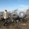 Beck Diefenbach  -  bdiefenbach@daily-chronicle.com<br /> <br /> Lee Miller tosses debris into the smoldering remains the horse barn which burned down Thursday on his family's ranch in Clare, Ill., on Friday Feb. 6, 2009.