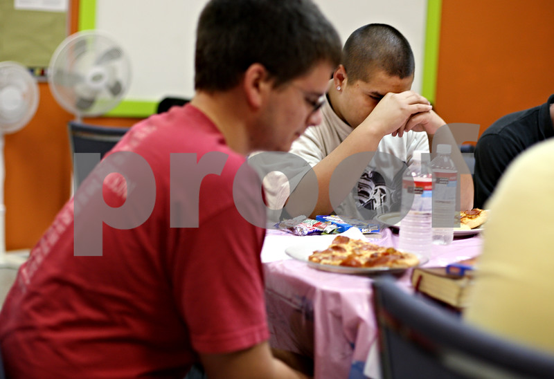 Beck Diefenbach  -  bdiefenbach@daily-chronicle.com<br /> <br /> Right, Justin Roscellie, 17, of DeKalb, prays during grace before starting a pizza party and faith lesson with local youths at the Salvation Army in DeKalb, Ill., on September 2, 2009.