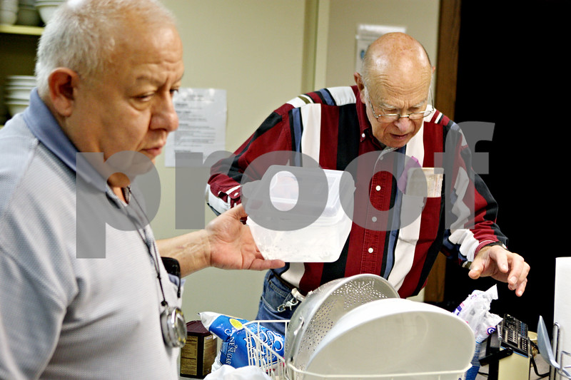 """Rob Winner – rwinner@daily-chronicle.com<br /> Joe Villa (left) takes a container from Warren Lowe while the two work together preparing a Christmas dinner at the Sycamore United Methodist Church in Sycamore, Ill. on December 24, 2009. Lowe, a Sycamore resident, recently placed a classified ad in the Daily Chronicle, looking for roommates. He wants them all to be fellow senior citizens so they """"could help take care of each other."""""""