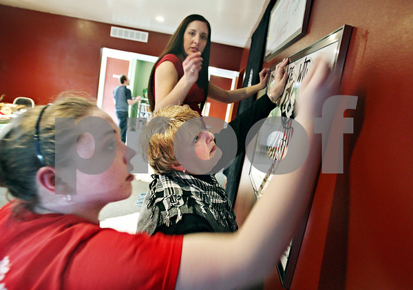 Beck Diefenbach  -  bdiefenbach@daily-chronicle.com<br /> <br /> Northern Illinois University students  Brittany Sheldon, left, and Christina Altergott, top, help Pastor Diane Dardon hang a poster for the Memory Wall at the Lutheran Campus Ministry in DeKalb, Ill., on Thursday Feb. 14, 2009.